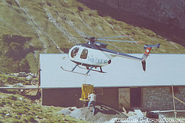 Swiss Alps, 1970s - The Hughes 500D HB-XFR of the elvetic operator Robert Fuchs trasports a bucket of gravel to a mountain hut (family Kolesnik)