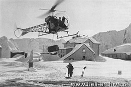 St. Gotthard Pass/TI, February 1955 - The Bell 47G HB-XAE in service with Heliswiss transports an oil drum (H. B. Burgunder - brochure Heliswiss)