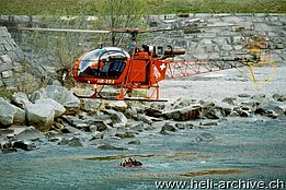 Lodrino/TI, March 2003 - Heli-TV SA 315B Lama HB-XRA descends over the Ticino river to refill its bumby bucket (M. Bazzani)