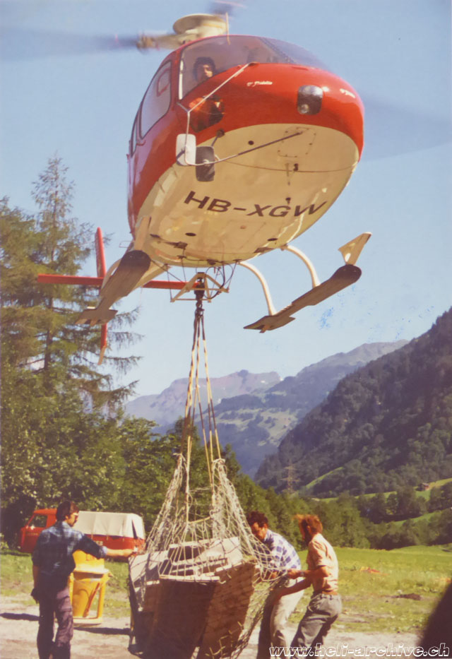 Glarus Alps, early 1980s - The AS 350B Ecureuil HB-XGW piloted by Peter Kolesnik transports a net of building material (family Kolesnik)