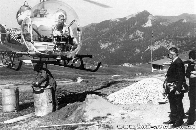 Image 3 - A mechanic hooks the bucket with the gravel to the barycentric hook of the Agusta-Bell 47G3B-1 HB-XCI piloted by Georg Wedtgrube (HAB)