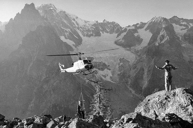 Image 6 - The Agusta-Bell 204B HB-XCQ at work in Val Veny. The man on the rock with hand signes gives the necessary indications to the pilot (P. Füllemann)