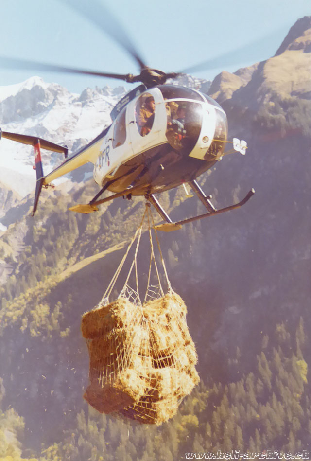 Swiss Alps, 1970s - The Hughes 500D HB-XFR of the helvetic operator Robert Fuchs transports a net containing hay (family Kolesnik)