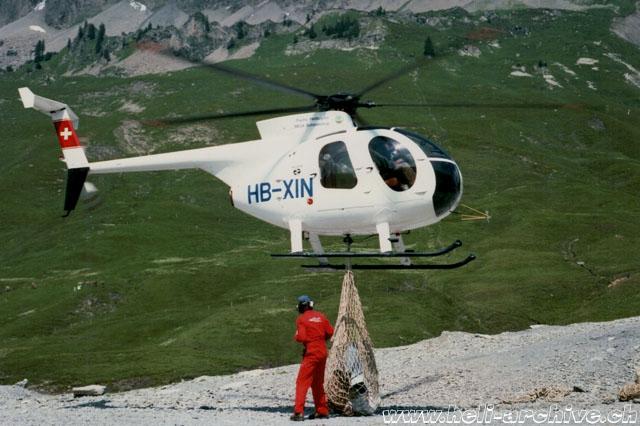 Swiss Alps, early 1980s - The Hughes 500D HB-XIN of the Swiss operator Robert Fuchs transports a net of supplies (HAB)