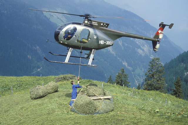 Swiss alps, early 1980s - The Hughes 500D HB-XKU of the Swiss operator Robert Fuchs transports a net of hay (HAB)