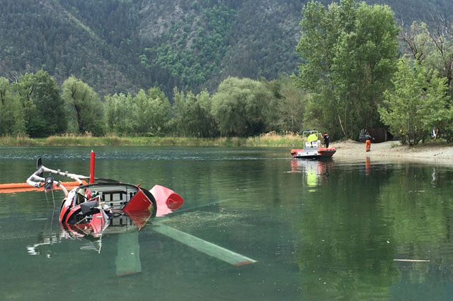 The wrackage of the AS 350B3+ Ecureuil HB-ZKF half submerged in the waters of the Baggersee (KAPO Wallis)